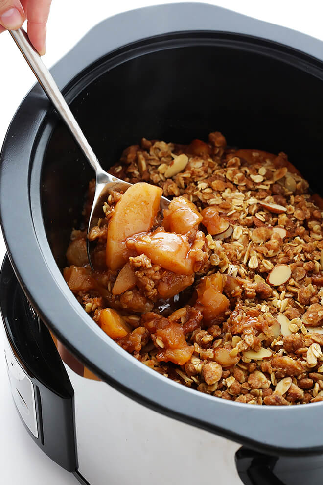 This Slow Cooker Apple Crisp recipe is made with a delicious warm cinnamon apple filling, and topped with a crispy oatmeal almond topping. So delicious, and perfect for fall and the holidays!