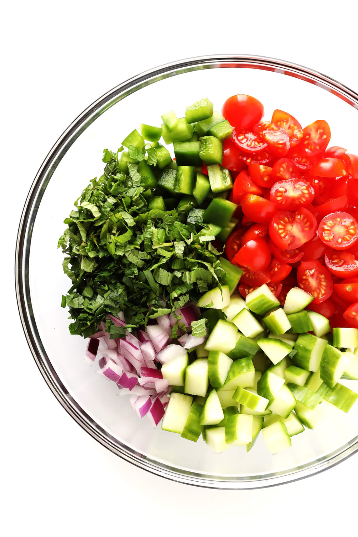 This delicious Israeli Salad recipe is quick and easy to make, full of the fresh flavors of tomatoes, cucumbers, peppers, mint, parsley and sumac, and it's so delicious! Serve it up on its own, or use it to make a simple pita wrap or hummus dip!   gimmesomeoven.com