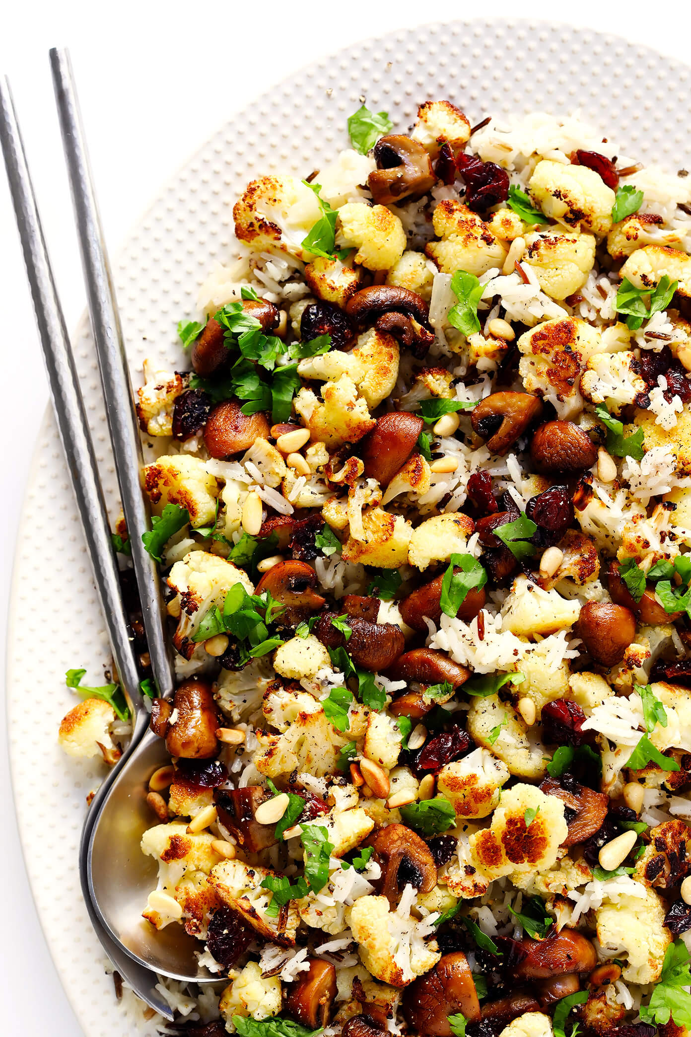 """This Roasted Cauliflower, Mushroom and Wild Rice """"Stuffing"""" is the perfect recipe to serve as a Thanksgiving side dish...or as dinner any night of the year! It's naturally gluten-free, vegetarian and vegan. It's made with delicious lemon-garlic rice, dried cranberries, toasted pine nuts, and roasted veggies. And it's AWESOME."""